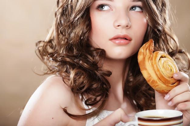 コーヒーとシナモンロールを持つ若い女性