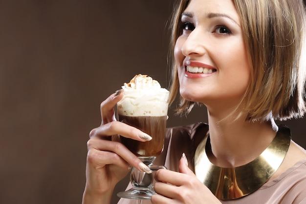 ホイップクリームとコーヒーのグラスを持つ女性