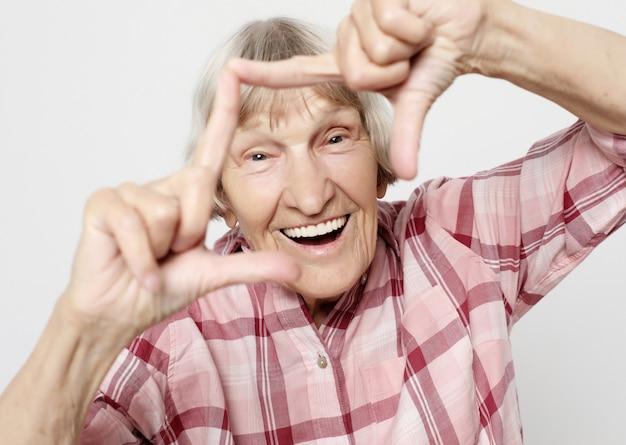 ライフスタイル、感情、人々の概念:ショックを受けた顔を持つ高齢の祖母。ピンクのシャツと祖母の肖像画。