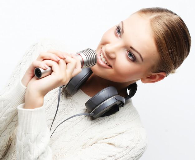 スタジオでヘッドフォンでマイクに向かって歌っている若い女性