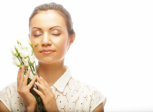 Молодая женщина с белыми цветами на белом