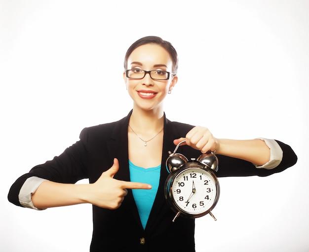 手に大きな時計を保持しているビジネス女性