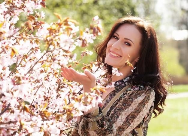 Образ жизни и люди концепции: красивая женщина в цветущем саду