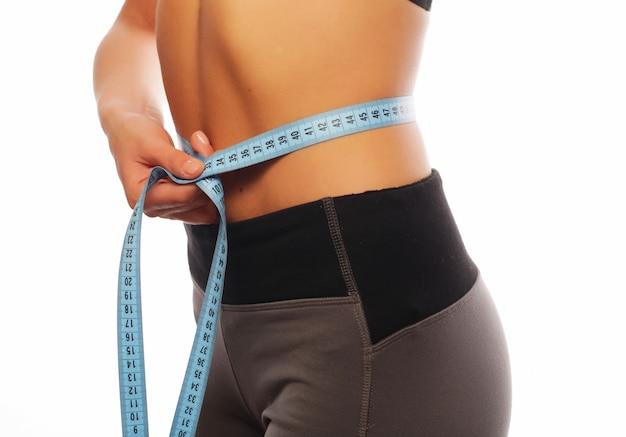 彼女の腰の測定スポーツウェアの女性のクローズアップ