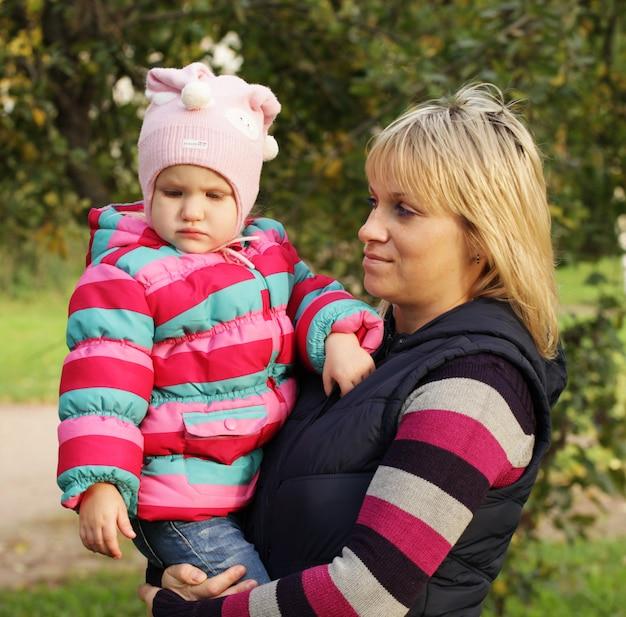 秋の公園で娘と一緒に幸せな母