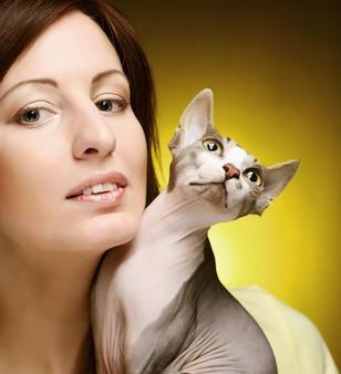 楽しいスフィンクス猫を持つ若い女