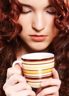 Красивая женщина пьет кофе на бежевом фоне