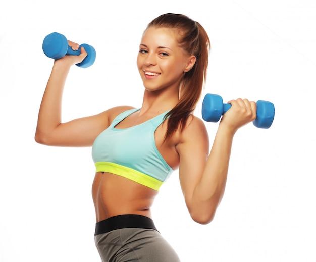 Женщина в спортивном инвентаре держит гантели