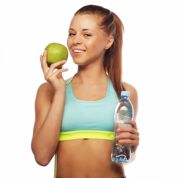 アップルと水のボトルとスポーツウェアの若い陽気な女性とスポーツ、ダイエット、健康、人々の概念