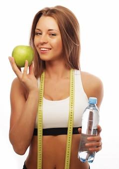 Молодая жизнерадостная женщина в спортивной одежде с яблоком и бутылкой воды
