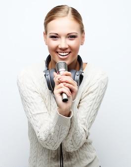 Молодая женщина поет в микрофон с наушниками в студии на белом