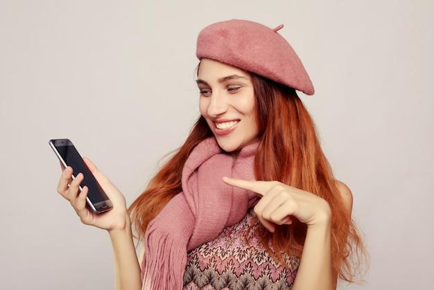 ライフスタイルと人々の概念:笑顔の女性がスマートフォンで指している