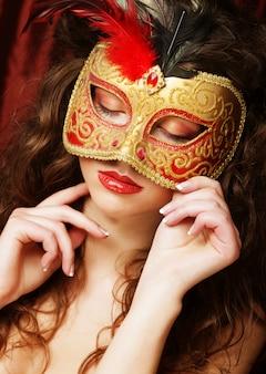 ベネチアの仮装カーニバルマスクを持つ女性
