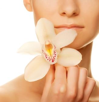 Девушка держит цветок орхидеи