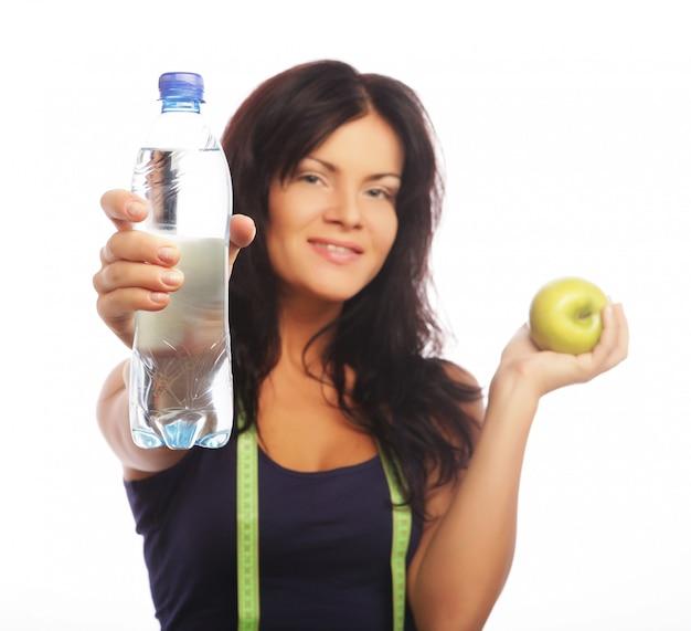 水のボトルと青リンゴを保持している女性のフィットネスモデル