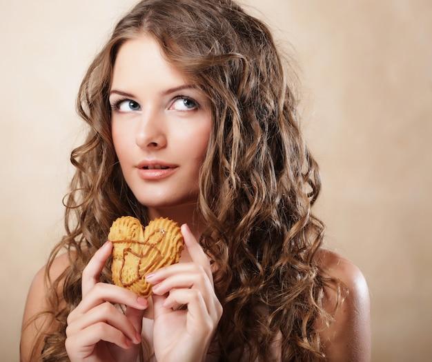ケーキと若い巻き毛の女性