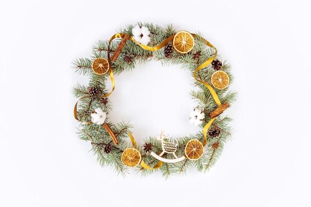 Круглая рамка, венок из еловых веток, сушеные апельсины, палочки корицы, звездчатого аниса, хлопковые цветы
