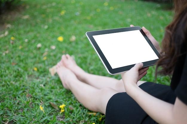 Женщина, используя планшет в саду