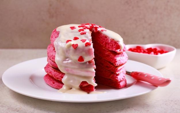 ホワイトチョコレートのトッピングと赤いパンケーキスタック