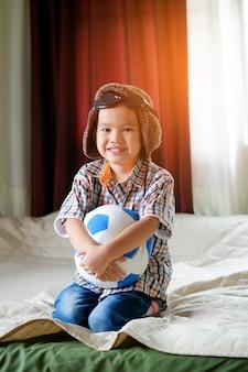 Маленький азиатский мальчик, играющий с мячом, концепция путешествия и приключений