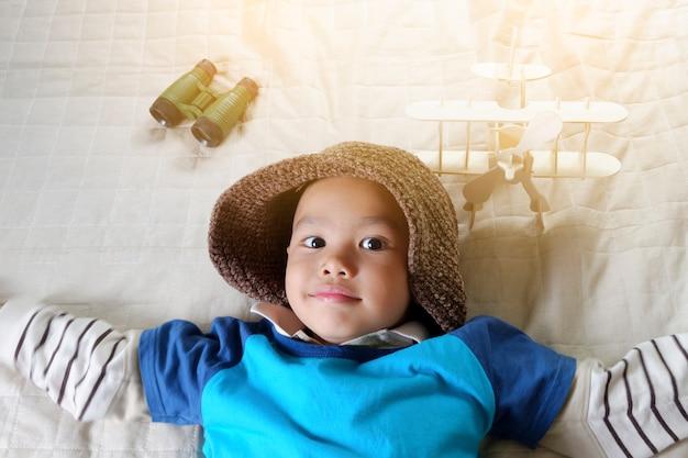 Счастливый парень, играющий с игрушечным самолетом, маленький азиатский мальчик любит путешествовать, концепция путешествия и приключений