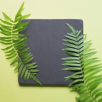 ノートブックと緑の植物と最小限のワークスペースデスクのフラットレイアウト