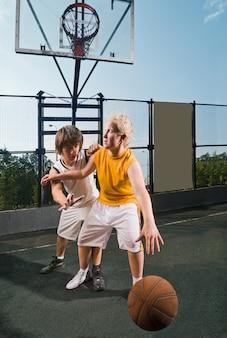 Два подростковых игрока с баскетболом