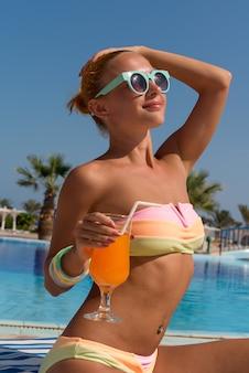 Счастливая молодая женщина с коктейлем