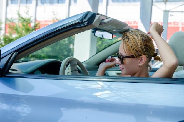 Красивая белокурая женщина за рулем своего кабриолета