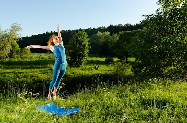Красная женщина, практикующих фитнес-йогу на открытом воздухе
