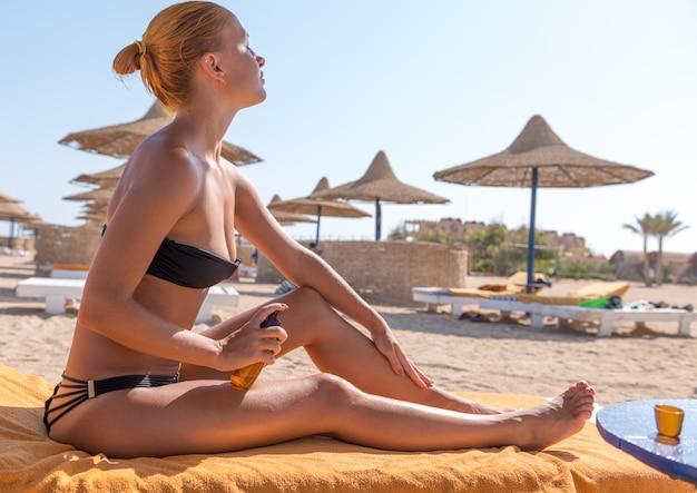 日焼け止め油を適用する敏感なスリムな女性