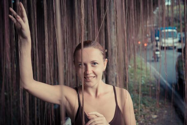 厚いジャングルの植生に立っている若い女性