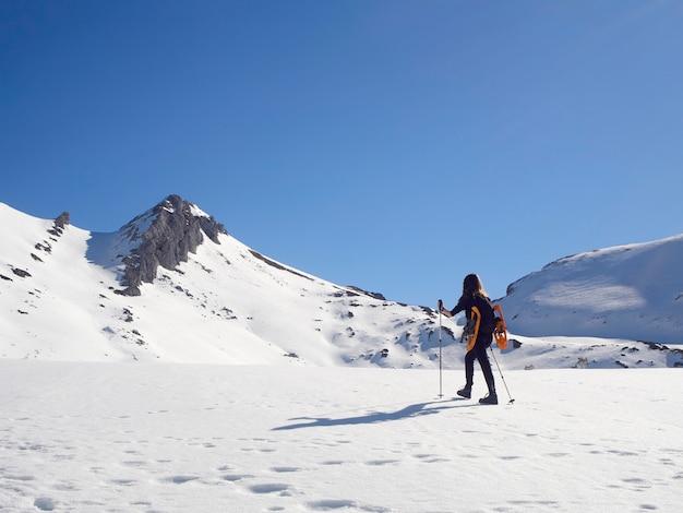 晴れた日にスペインのレオン、サンイシドロでスノーシューをする女性