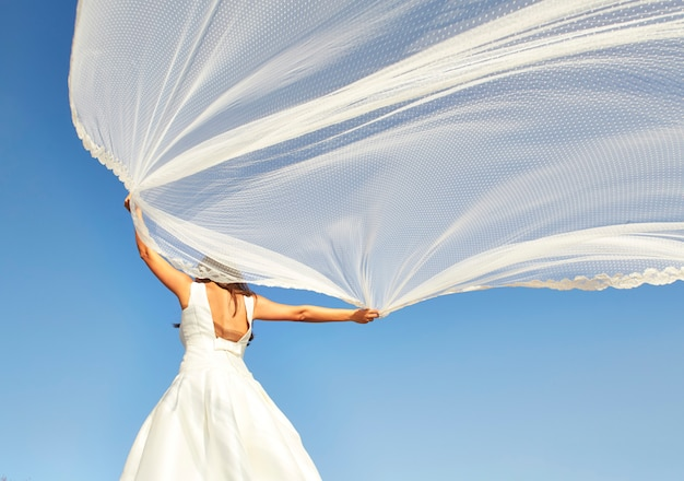 Невеста держит вуаль на ветру