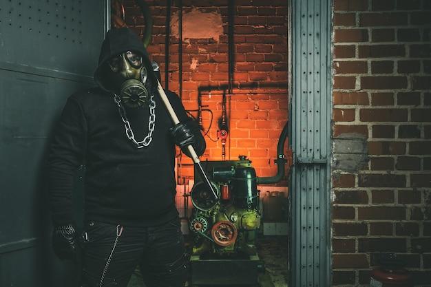 Человек с противогазом и молотком в машинном отделении. концепция ядерной, биологической и химической опасности.