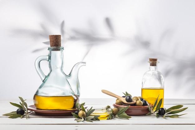 Оливковое масло и оливковая ветвь на деревянном столе