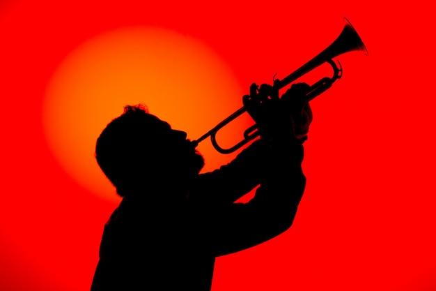赤い背景で分離されたトランペットを演奏するジャズミュージシャンのシルエット。ジャズ音楽のコンセプト。