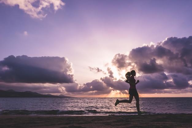 ビーチで走っている若い女性