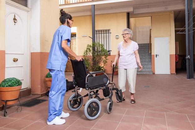 自宅で彼女の介護者と杖を持つ幸せな年配の女性