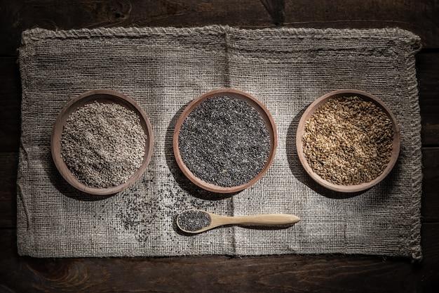 Семена кунжута, чиа и льна в деревянной посуде, деревянной ложкой с чиа на деревянной основе. вид сверху.