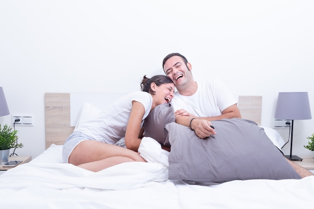 自宅のベッドで幸せな笑いリラックスした若いカップル。