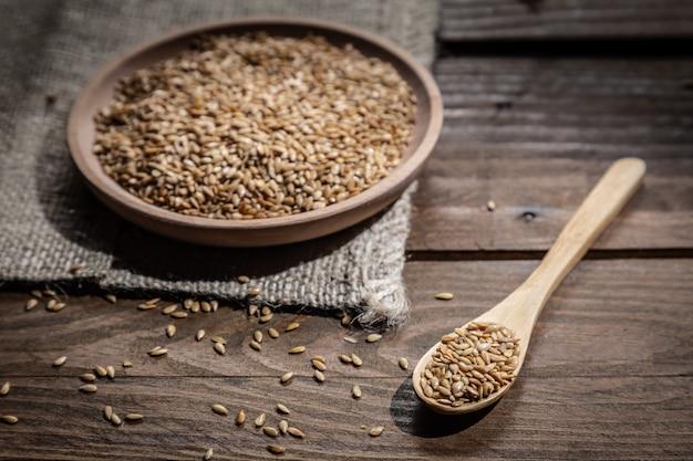 Семена льна на деревянной тарелке и деревянной ложкой