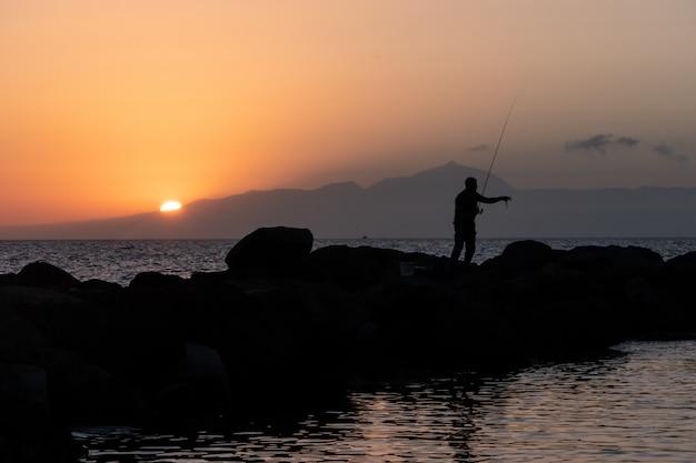 日没時の漁師シルエット釣り