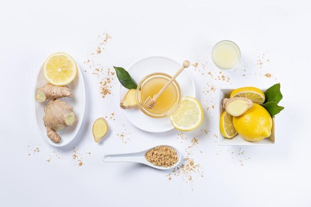 Имбирь, мед и лимон в белых тарелках и ложке
