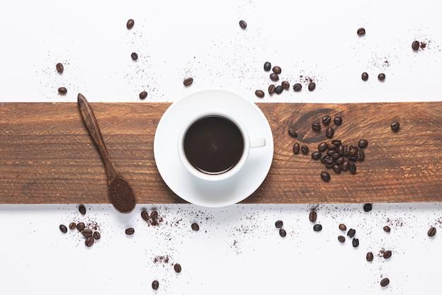 白いコーヒーカップ、こぼれたコーヒー豆、コーヒーと木のスプーン