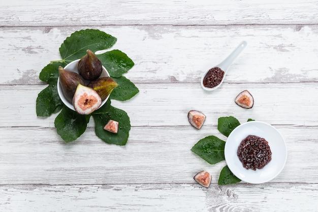 イチジクの葉とイチジクのジャムと木製のプレートに新鮮なイチジク