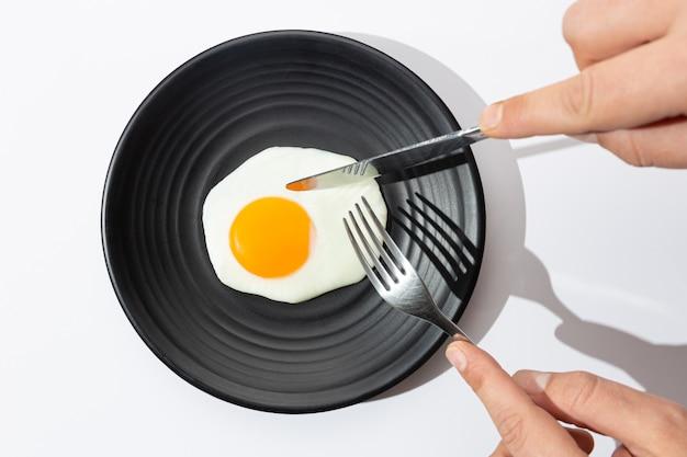 Руки собираются съесть с ножом и раскошелить яичницу на черной тарелке.