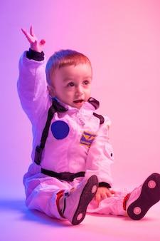 赤と青の光で照らされたアメリカの宇宙飛行士の服を着ている男の子のカラフルな肖像画。宇宙飛行士と子供の概念。