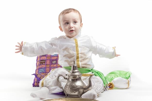 Кавказский маленький мальчик, одетый как араб, пьет чай.