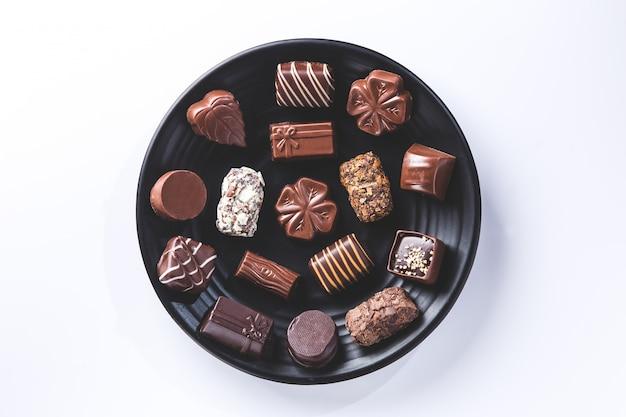 白で隔離されるプレート上のさまざまなチョコレートプラリネ。甘いチョコレート。